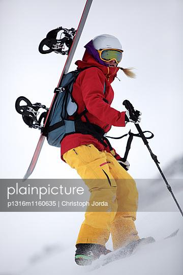 Junge Snowboarderin steigt durch den Schnee in den Bergen, Pitztal, Tirol, Österreich - p1316m1160635 von Christoph Jorda