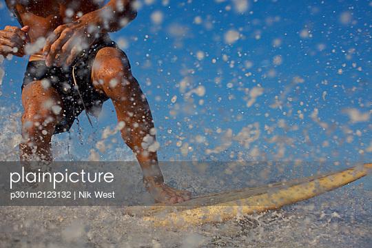 Male surfer riding ocean wave, splashing - p301m2123132 by Nik West