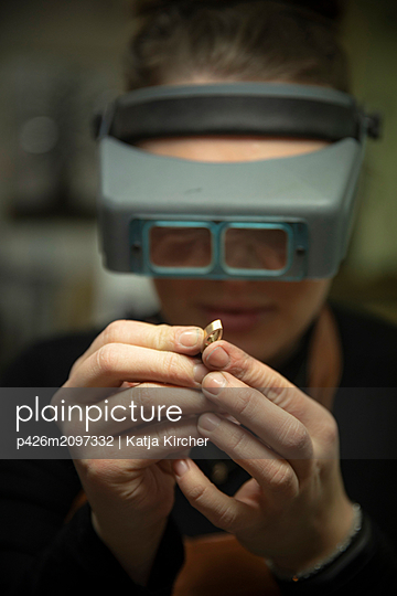 Female goldsmith looking at gold through headband magnifier in workshop - p426m2097332 by Katja Kircher