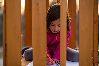 A little girl sits on playset at sunset writing with paper and pencil - p1166m2136587 by Cavan Images