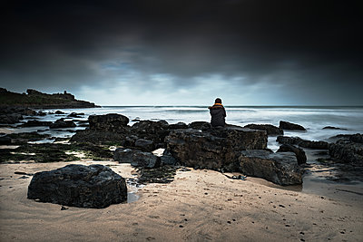 Girl in Black Looking Out To Sea Sitting on Rocks - p1166m2205751 by Cavan Images
