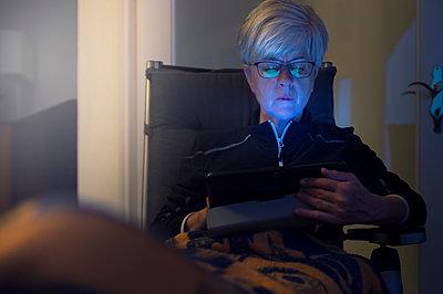 Senior woman sitting in armchair using digital tablet - p300m1487376 by Frank Röder