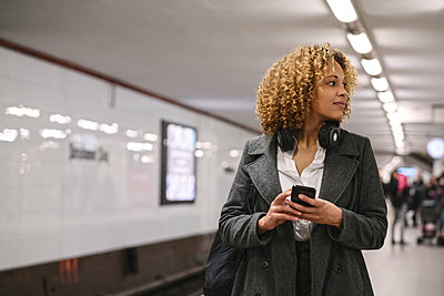 Woman with cell phone waiting in subway station - p300m2143426 by Hernandez and Sorokina