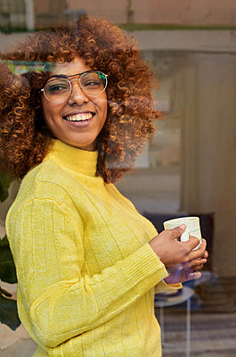 Smiling woman with coffee cup day dreaming behind glass at cafe - p300m2243386 by Veam