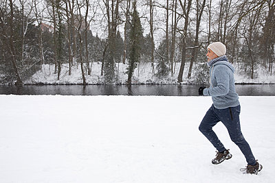 Man running on snow at park during winter - p300m2281917 by Frank van Delft
