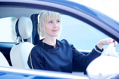 Frau im Auto blickt in den Spiegel - p606m2031395 von Iris Friedrich