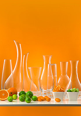 Vases and jugs of glass with citrus fruit on an orange background   - p8476791 by Klara G