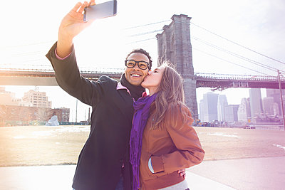 Young couple taking self portrait next to Brooklyn Bridge, New York, USA - p924m930579f by Chad Springer