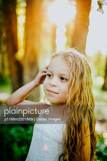 Bright vertical portrait of young girl with hand in her hair - p1166m2201869 by Cavan Images