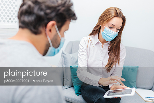 Doctor wearing face mask using digital tablet while sitting by man at office - p300m2227001 by Manu Reyes