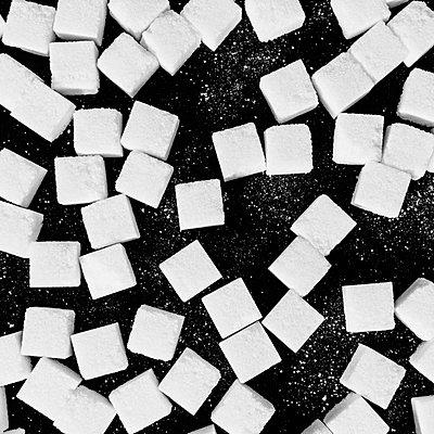 Overhead view of sugar cubes on black backdrop - p1100m887981f by Paul Edmondson
