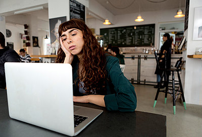 Frustrated young woman using laptop in a cafe - p300m2103267 by FL photography