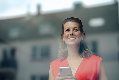 Smiling businesswoman with smart phone looking through window - p300m2242692 by Gustafsson
