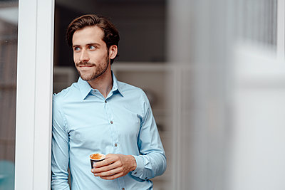 Businessman with disposable coffee cup leaning on door - p300m2300260 by Kniel Synnatzschke