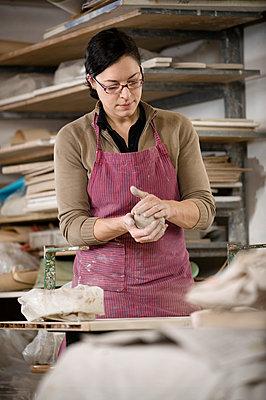Germany, Bavaria, Mid adult woman making model of clay in workshop - p300m879250 by Robert Niedring