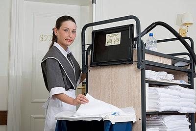 Uniformed maid standing next to push cart in hotel corridor - p301m976055f by Halfdark