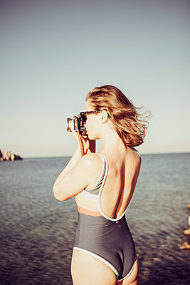 Woman in swimsuit takes pictures at the seaside - p713m2284045 by Florian Kresse
