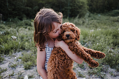 Girl kissing puppy in her arms - p924m2016300 by Kymberlie Dozois Photography