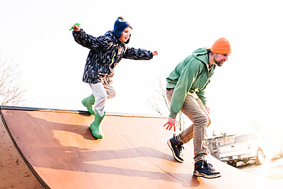 Boy chasing father on skateboard ramp, low angle view - p924m2097764 by Viara Mileva