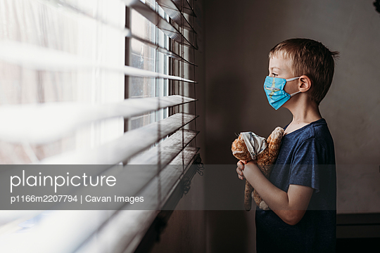 Side view of young school aged boy with mask on with stuffed animal - p1166m2207794 by Cavan Images