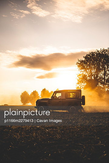 An all terrain vehicle drives in a field - p1166m2279413 by Cavan Images