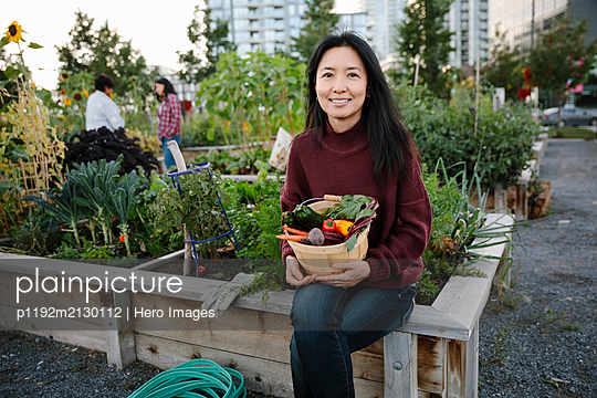 Portrait happy woman harvesting fresh vegetables in community garden - p1192m2130112 by Hero Images