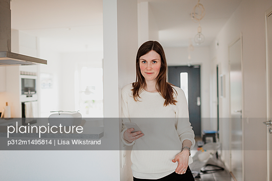 Young woman holding cell phone - p312m1495814 by Lisa Wikstrand