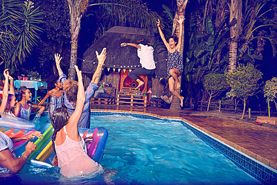 Young friends playing, jumping into swimming pool at night - p1023m2187432 by Trevor Adeline