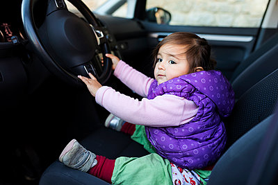 Cute toddler holding a steering wheel sitting on a driver's seat - p1166m2094912 by Cavan Images