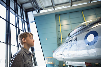 Curious boy viewing Air Force airplane in war museum hangar - p1192m1447253 by Hero Images