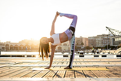 Asian woman practicing yoga on a pier at harbour at sunset, dancer pose - p300m2144279 von Rafa Cortés