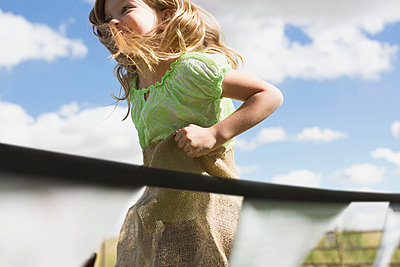 Young girl participating in a potato sack race. - p328m784044f by Hero Images