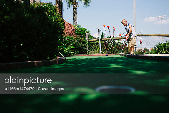 Boy playing miniature golf against sky
