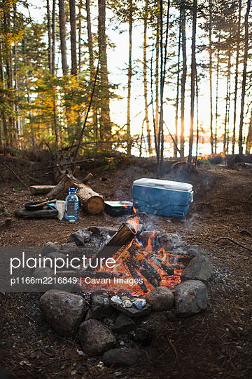 Campfire at sunset while car camping in coastal Maine - p1166m2216849 by Cavan Images