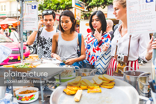 Thailand, Bangkok, Khao San Road, group of friends choosing local food on street market - p300m1581336 von William Perugini
