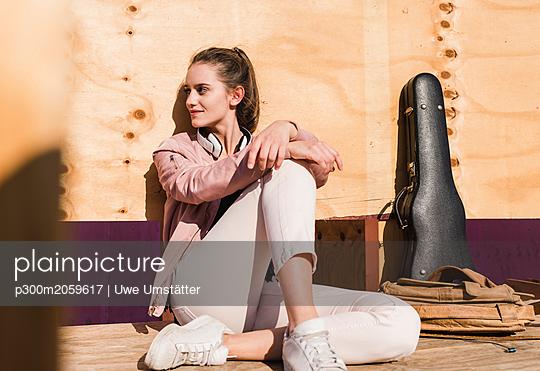 plainpicture - plainpicture p300m2059617 - Relaxed young woman sitting... - DEEPOL by plainpicture/Uwe Umstätter