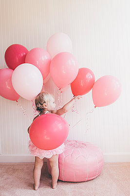 Toddler girl playing with balloons - p1086m1154431 by Carrie Marie Burr