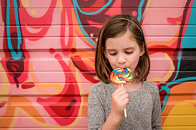 a young girls eats a huge rainbow lollipop in front of a colorful wall - p1166m2212486 by Cavan Images