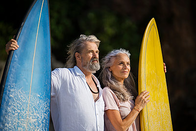 Affectionate senior couple with surfboards at beach - p300m1549621 by Steve Brookland