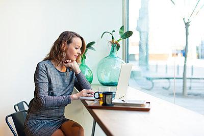 Mature businesswoman using laptop in a cafe - p300m2104026 von Javier Pardina