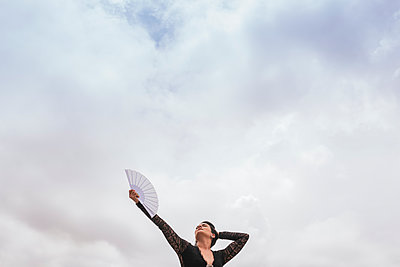 Female dancer with hand fan performing flamenco under cloudy sky - p300m2273957 by MORNINGVIEW AGENCY