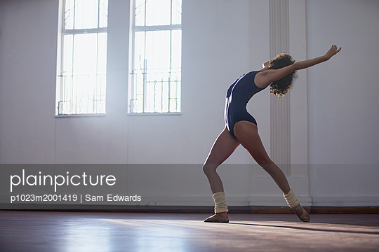 Graceful young female dancer practicing in dance studio - p1023m2001419 by Sam Edwards