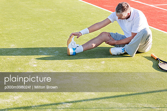 Tennis player sitting on tennis court stretching leg