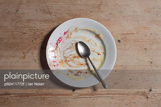 Remains of eaten pudding on plate - p92411772f by Ian Nolan