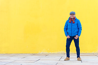 Confident senior man in casual clothes standing against yellow wall - p1166m2084713 by Cavan Images