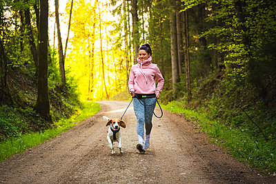 Young woman and dog running together in sunny forest. - p1166m2285793 by Cavan Images