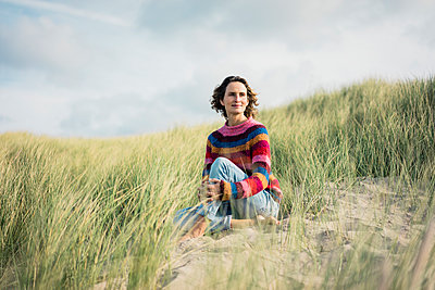 Mature woman relaxing on the beach, sitting in the dunes - p300m2059459 von Robijn Page