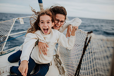 Laughing mother with excited daughter on sailboat during vacation - p300m2274854 by Gala Martínez López