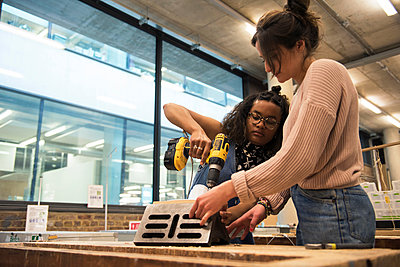 Students in art studio assembling object using cordless screwdriver - p429m1513856 by G. Mazzarini
