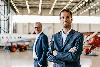 Two businessmen in aircraft hangar - p586m1208566 by Kniel Synnatzschke